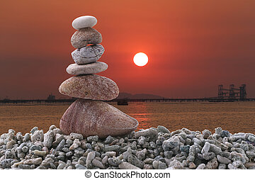 Balance stone on pile rock of sunset background in the evening.