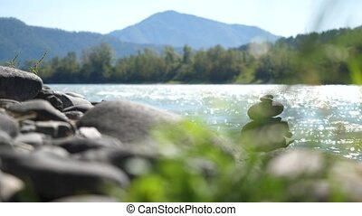 Balance stone on river coast in nature landscape on Altai...