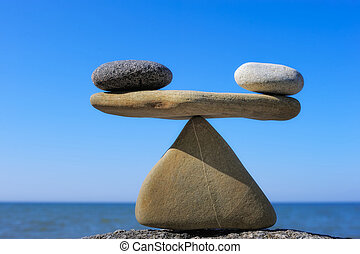 Symbol of scales is made of pebble on the cliff