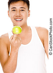 A male asian model balances an apple on his finger