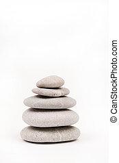 Balanced grey stones over white background