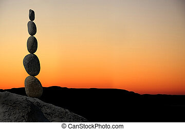 Balanced stack of stones at sunset.