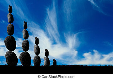 Balanced stone statues against a striking blue sky.