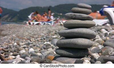 balanced stones stack on pebble beach, defocused people in...