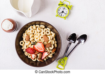 Balanced traditional breakfast. Whole grain rings cheerios, berries and egg on white table.