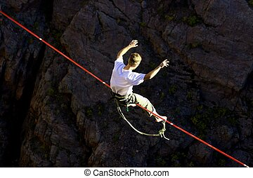 Slack line walker sits to regain his balance before continuing his precarious walk over 1100 ft. drop at Royal Gorge in Colorado.