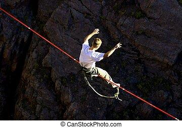 Balancing Act - Slack line walker sits to regain his balance...