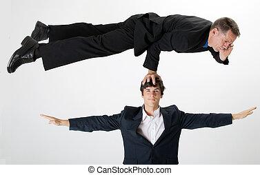 Balancing businessman talking on phone