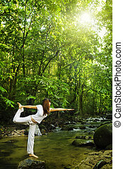Female practises balancing at nature tropical forest in a morning.