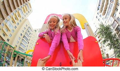 Little twins walking on child%u2019s bridge