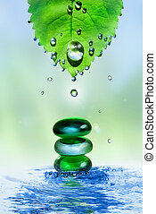 balancing spa shiny stones in water splash with leaf and...