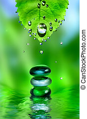 balancing spa shiny stones with leaf and water drops on...