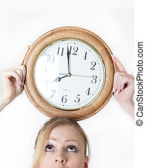 balancing time - woman with a clock balanced on head showing...