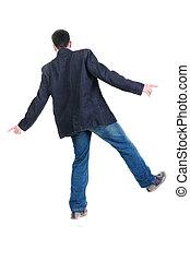 Balancing young man in jacket. Rear view.