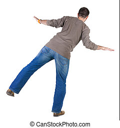Balancing young man . Rear view.