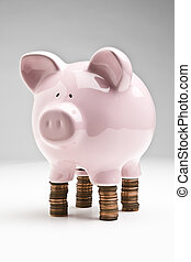 Balancing your budget - Piggybank placed on stacks of...