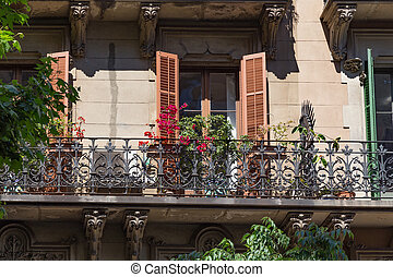 Balconies with flowers of the one of old buildings in modern style in the historical center of Barcelona in sunny day. Spain.