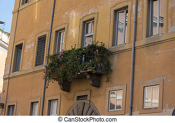 Balcony in the city of Rome overgrown with flowers.