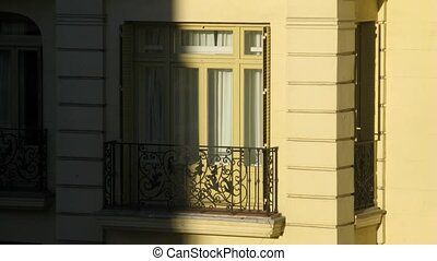 Balcony of building disappears in shadow from sun, time lapse