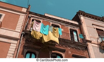 Balcony on the red brick facade with towels hanging on the rope