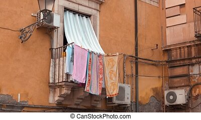 Balcony on the red brick facade with towels in Italy
