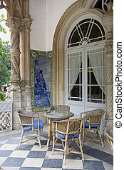 A balcony with resting chairs and a coffe table, in the Bussaco Palace, in Portugal.