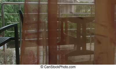 View from hotel room through the open door to balcony with wet outdoor table and chairs set during heavy rain