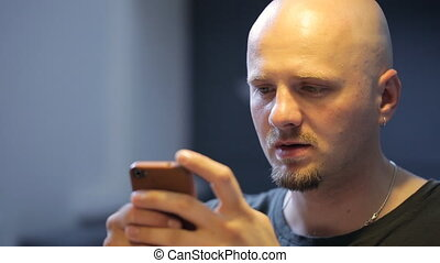 Bald bearded man chats in smartphone sitting in art studio....