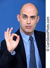 Bald businessman making ok gesture