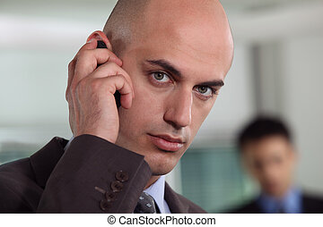 Bald businessman making telephone call