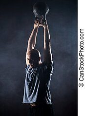 Bald charismatic athlete doing kettlebell swings. Studio...