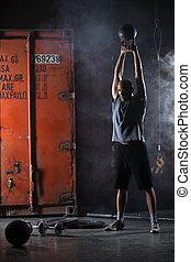 Bald charismatic athlete doing kettlebell swings. Studio shot in