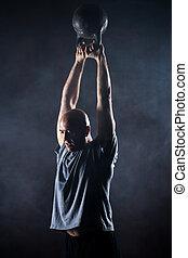 Bald charismatic athlete doing kettlebell swings. Studio...