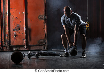 Bald charismatic athlete doing squats with weights. Studio...