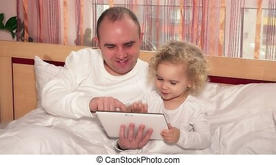 bald father with little cute daughter girl play game on tablet computer in bed