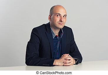 bald guy sits at the desk