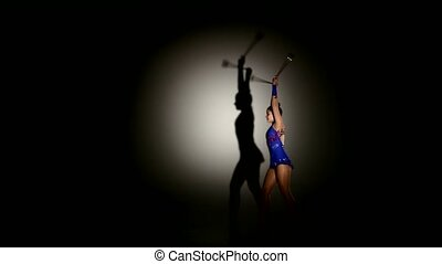 Bald-headed girl juggles on dark background