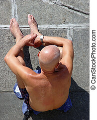 Bald man sunbathing