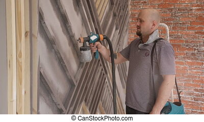 Bald man using a spray gun to paint the facade of the house.