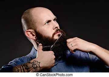 Bald man with a beard shortens his beard - grey background