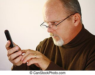 Bald man with glasses looking at cell phone.