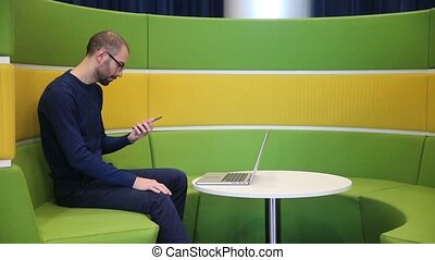 Bald man with glasses working on laptop with phone