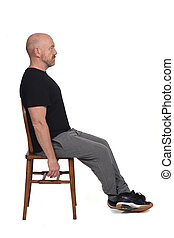 Bald man with sportswear sitting on a chair on white background.