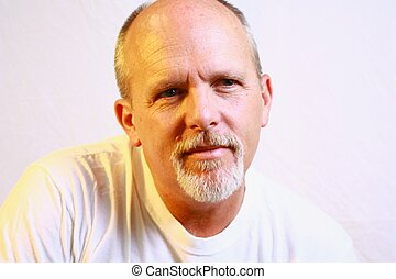 Bald man with white goatee and white shirt.