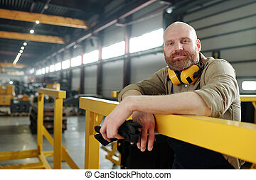 Bald manual worker at factory