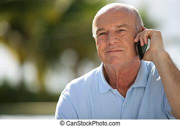 Bald senior making a call from the garden