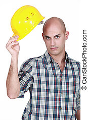Bald young builder lifting hat