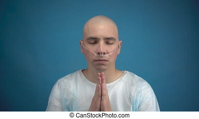 Bald young man with oncology looks at the camera and prays on a blue background. The patient folded his hands and prays with a smile. Hair loss due to chemotherapy. 4k