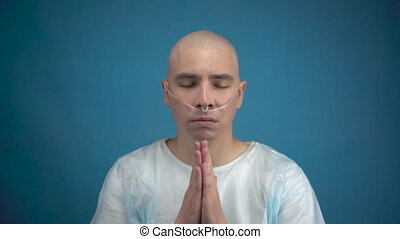 Bald young man with oncology looks at the camera and prays on a blue background. The patient folded his hands and prays. Hair loss due to chemotherapy. 4k