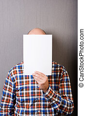 Balding man holding a blank paper in front of face